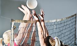 Girls blocking a volleyball at the net