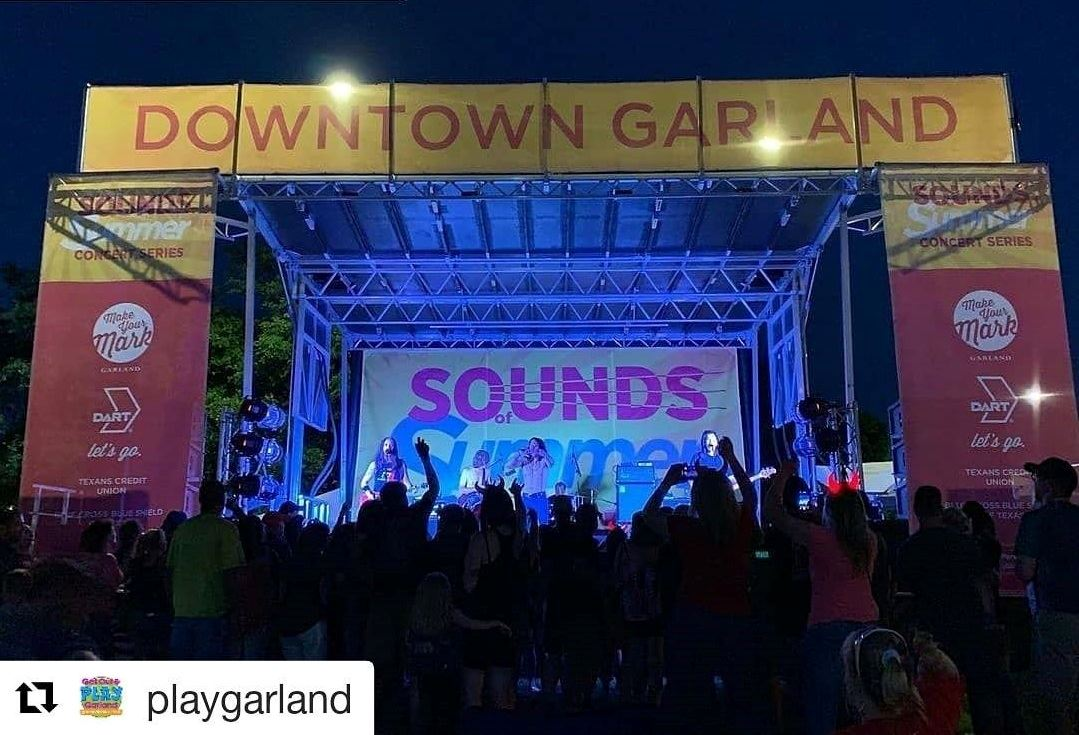 "Concert Stage in the Square with banners ""Downtown Garland"" and band playing on stage."